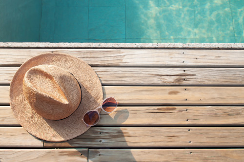 Top view of poolside, sun hat and sunglasses on wooden floor