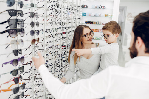 Mother with cute son. Family buy glasses. Assistant helping the clients